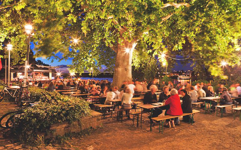 People sat in an outdoor beer garden at night