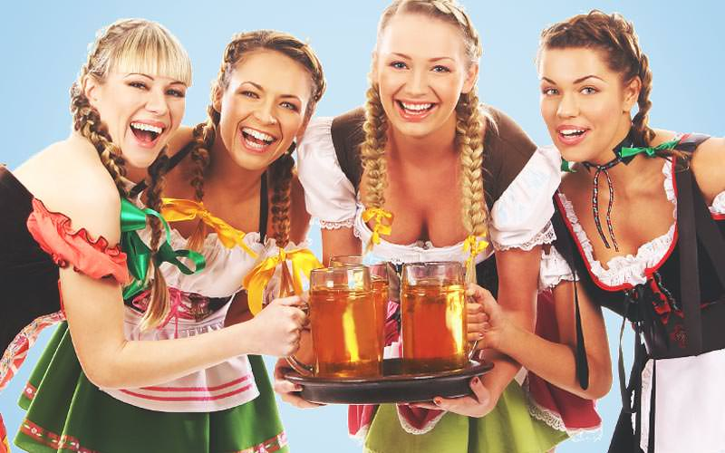 Four women holding steins on a tray and dressed as beer maids