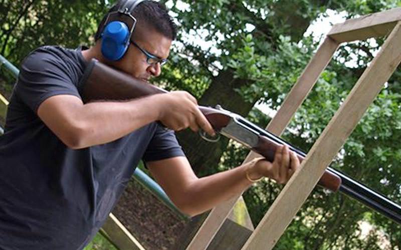 A man aiming a shotgun through a wooden frame