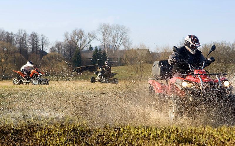 Line of three men driving quad bikes in a muddy field