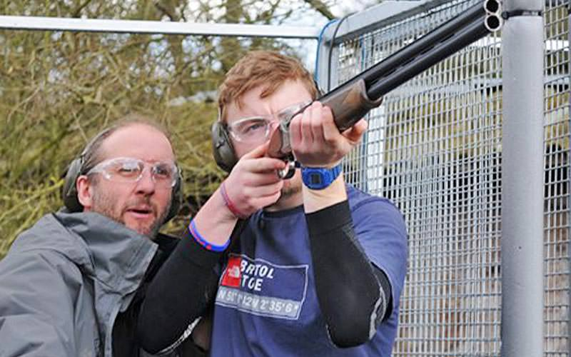 A man aiming a shotgun from a metal frame, with an instructor looking on