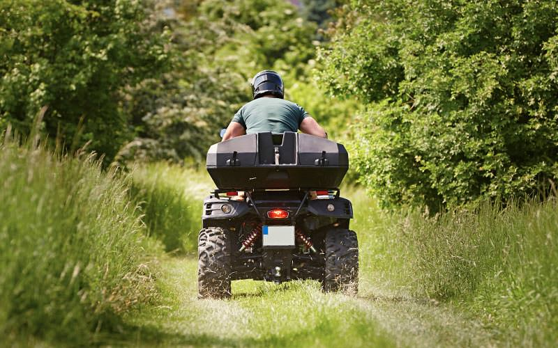 The back of a man driving a quad bike through a field