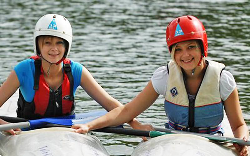 Two women sat in kayaks