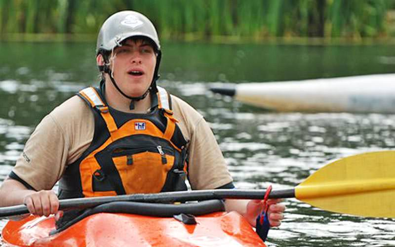 A man sat in a kayak and holding a paddle