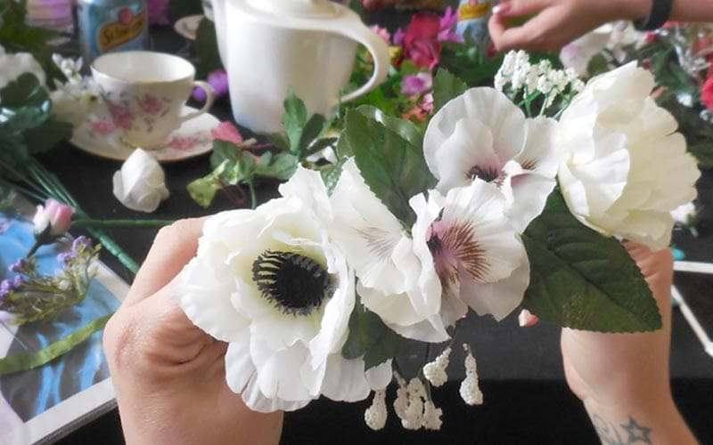 Close up of artifical white flowers being placed together