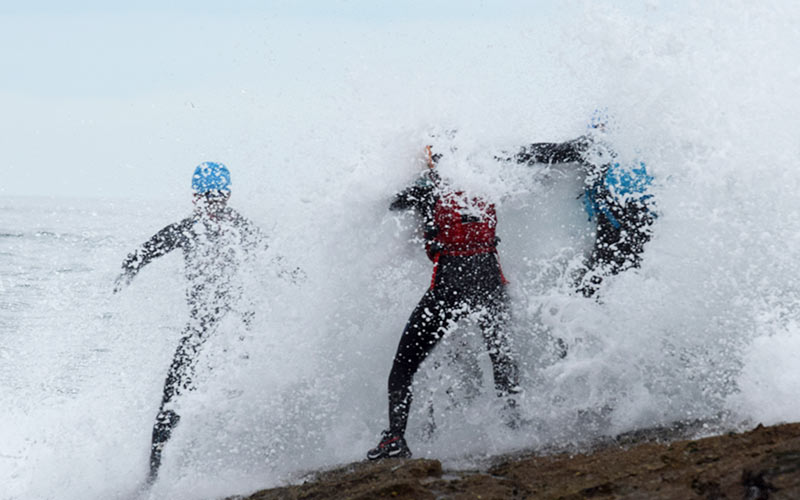 Three people getting splashed by a big wave