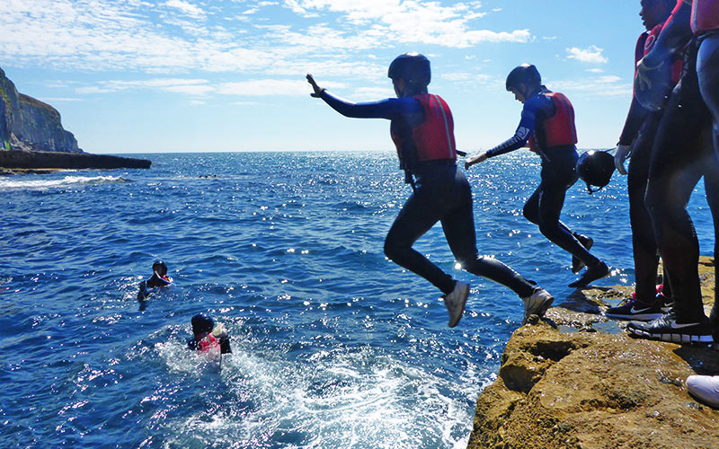 Two people about to jump off a rock into the sea