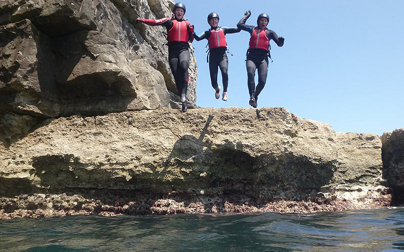 Three people jumping off a cliff face into the sea