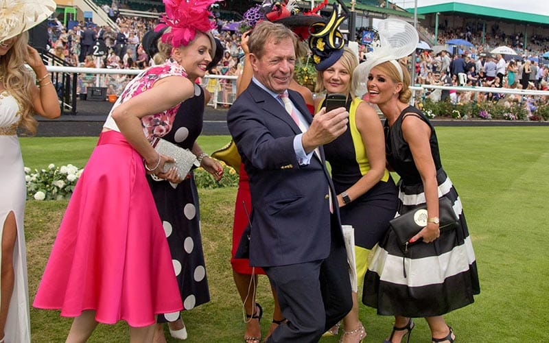 Man in a suit taking a selfie with a group of ladies dressed elegantly for race day, on the course with crowds in the background.
