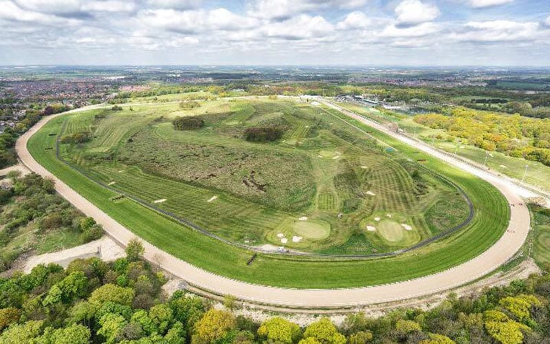 Aerial image of Newcastle Racecourse, with the track surrounded by lots of greenery and a blue cloudy sky.