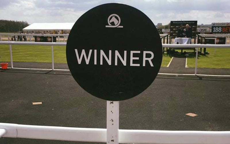 Image of the Newcastle Racecourse Winner sign, in front of the track and winners enclosure.