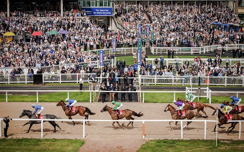 Horses passing the finishing post on the all weather track, with a large crowd behind all watching the action.