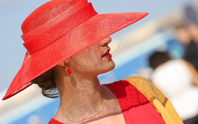 A woman in a brightly coloured hat and dress