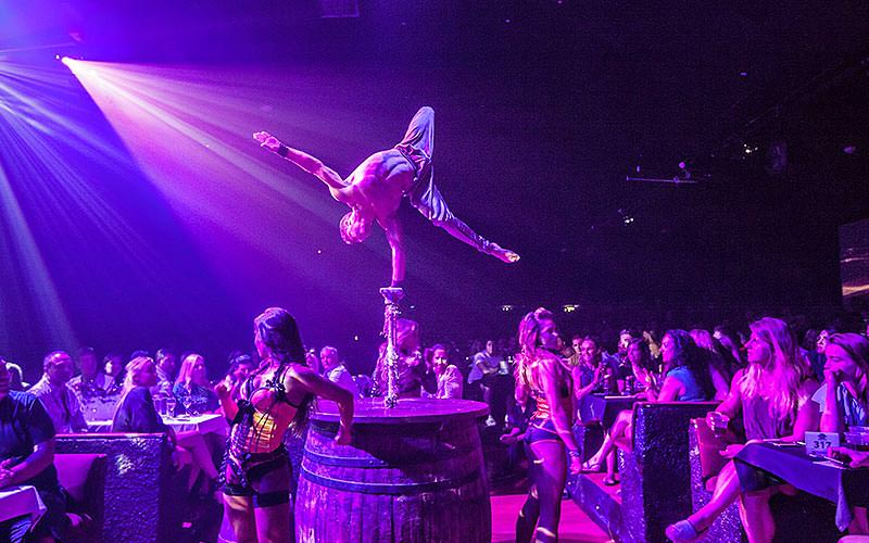 Man balancing on a barrel and performing to a crowd to a purple backdrop