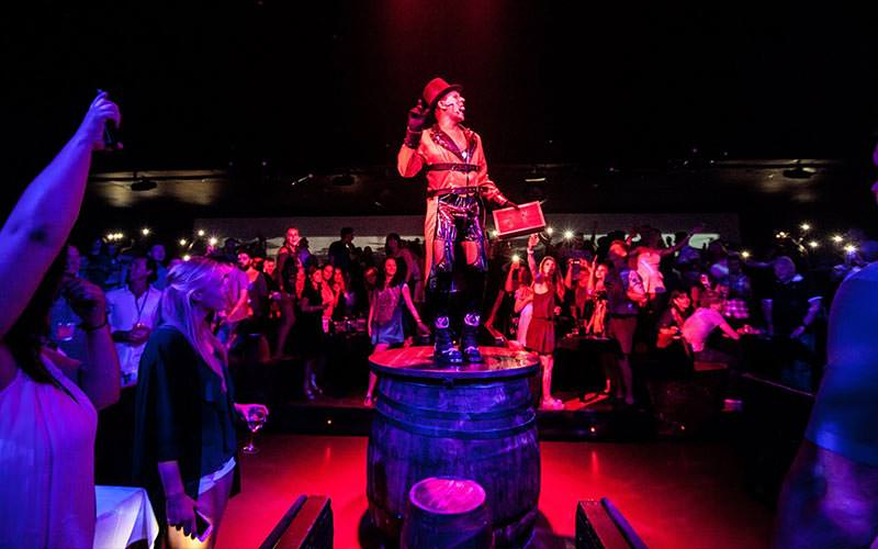 A man dressed in circus gear, stood on top of a barrell, and performing to a crowd