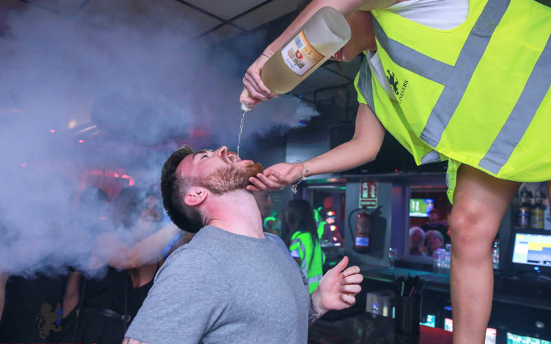 A woman pouring alcohol into a man's mouth