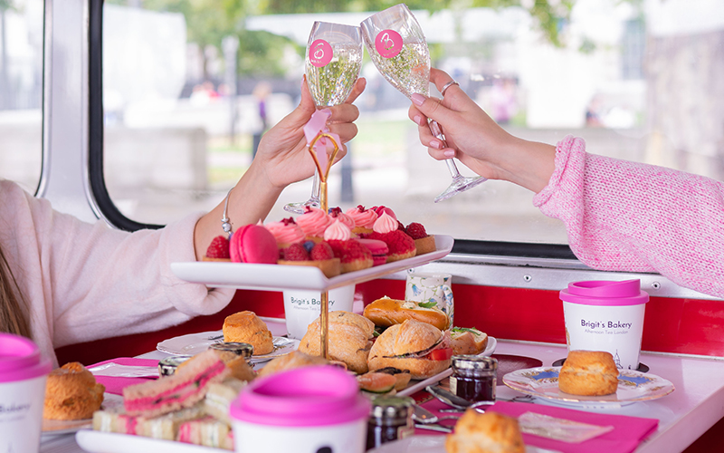 Afternoon tea set up on a bus on a white table, with two girls holding a glass of bubbly