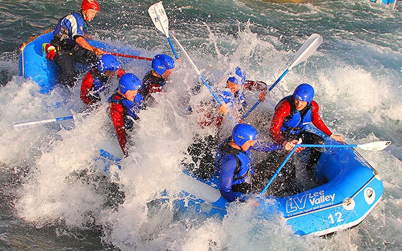 Blue raft with people on board being totally covered by water as they hit the rapids