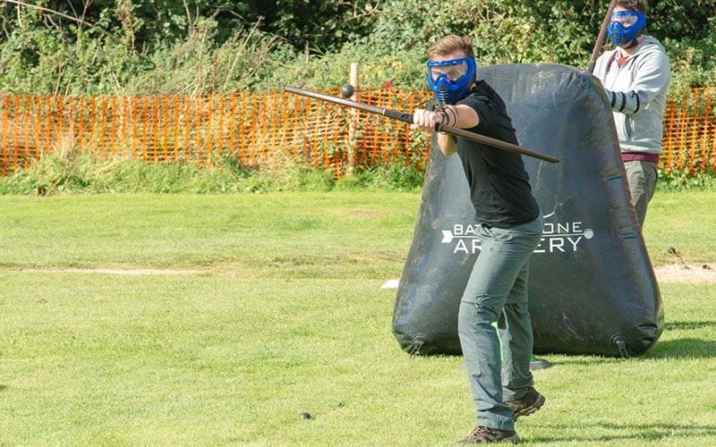 Man in a field shooting an arrow towards the camera, he is wearing a mask and behind him is an inflatable shield and man behind it.