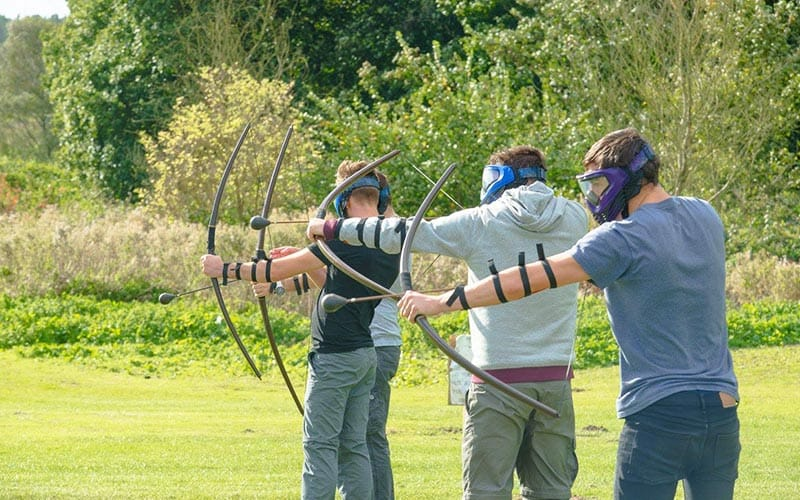 3 men wearing masks and all shooting their bow and arrows together.
