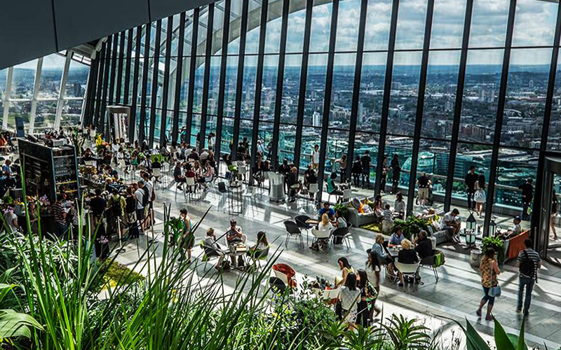 Grass plants and people sat on tables and chairs in the glass-walled The Shard, LondonWaiter carrying a tray of pink drinks
