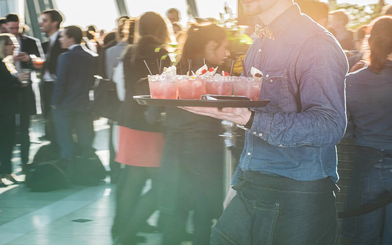 Waiter carrying a tray of pink drinks