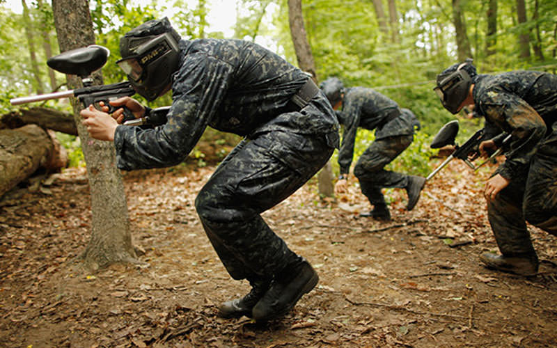 A group of men hiding behind a fence in an outdoor paintball field, whilst aiming with paintball guns