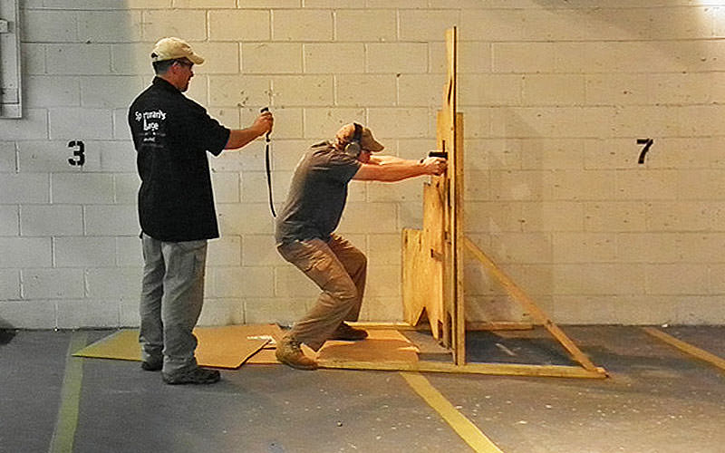 A man aiming a handgun through a wooden obstacle with a man standing behind