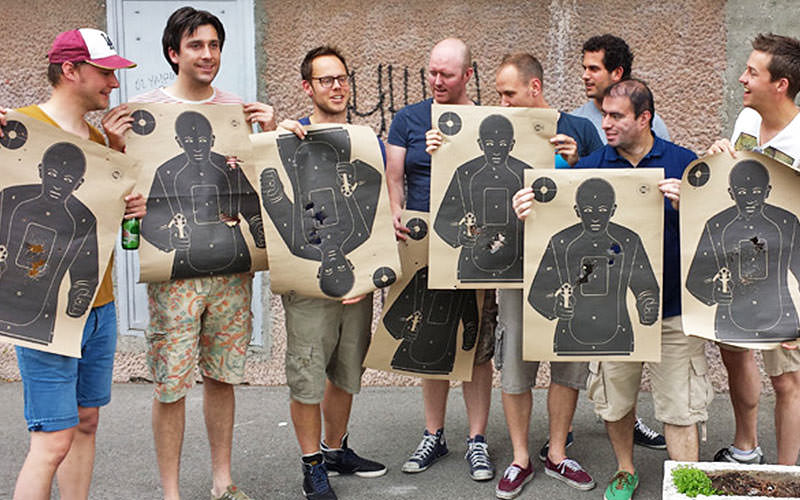 A group of men holding up their paper targets with bullet holes through them