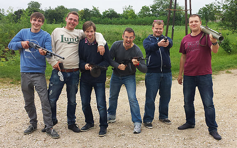 Six men posing outdoors with various firearms