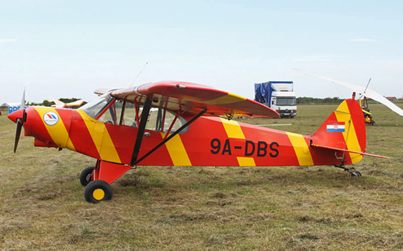 A red and yellow striped light aeroplane stationary on grass