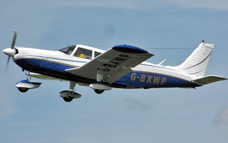 A blue and white light aircraft mid-flight
