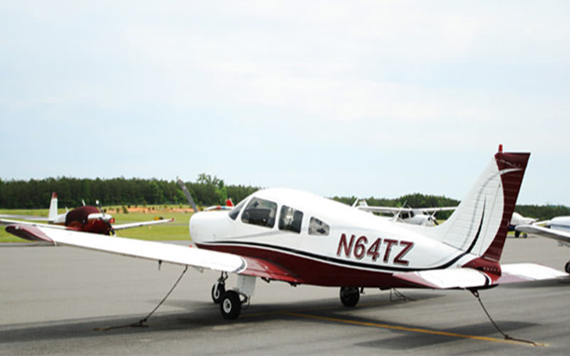 A red and white light aircraft stationary on tarmac