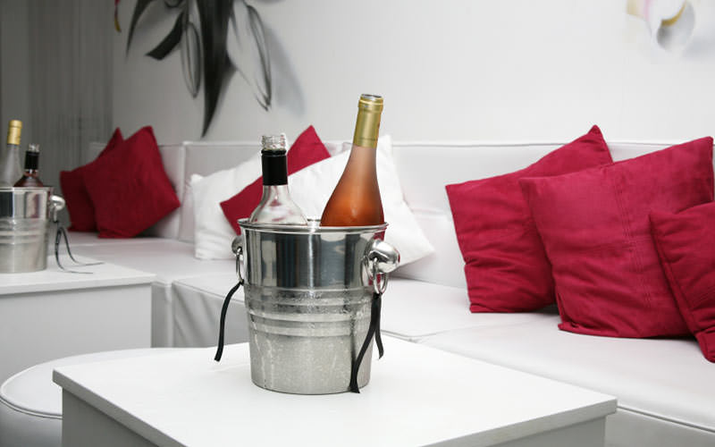 A metal ice bucket containing two bottles of wine on a white table in front of a long sofa bench
