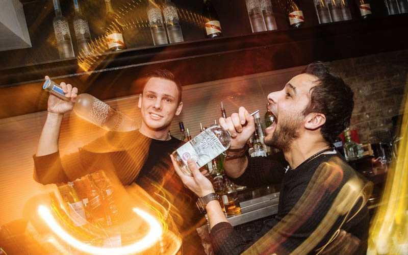 A man holding a large bottle of vodka, and another man pretending to drink from a large bottle