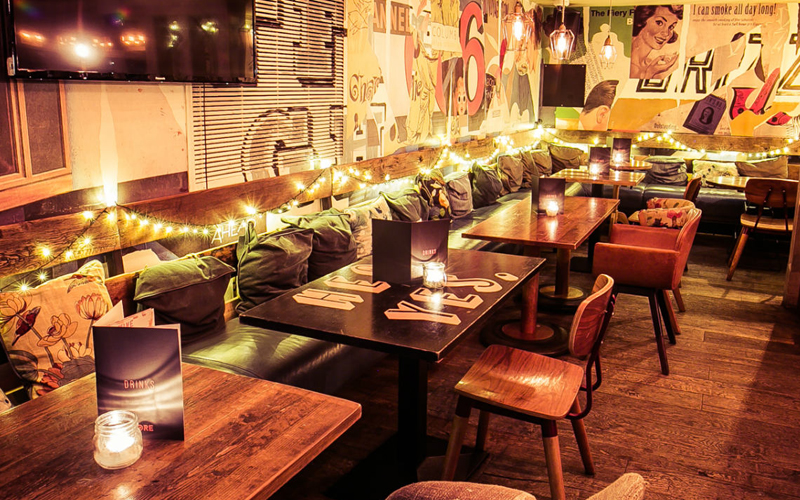 Several tables and chairs with lots of bright lighting in a bar