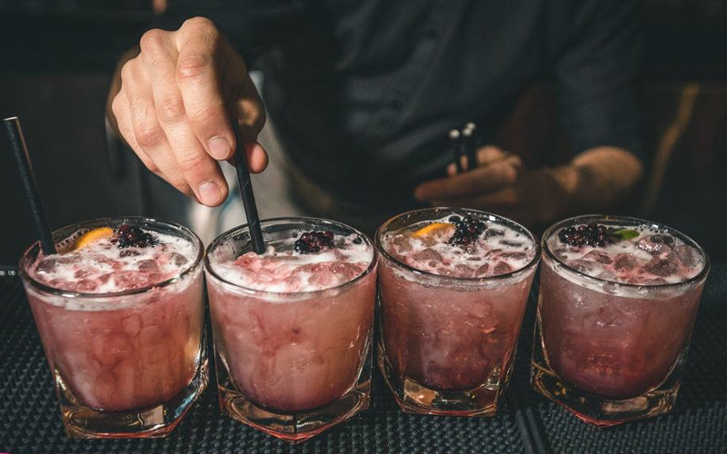 A man making four cocktails