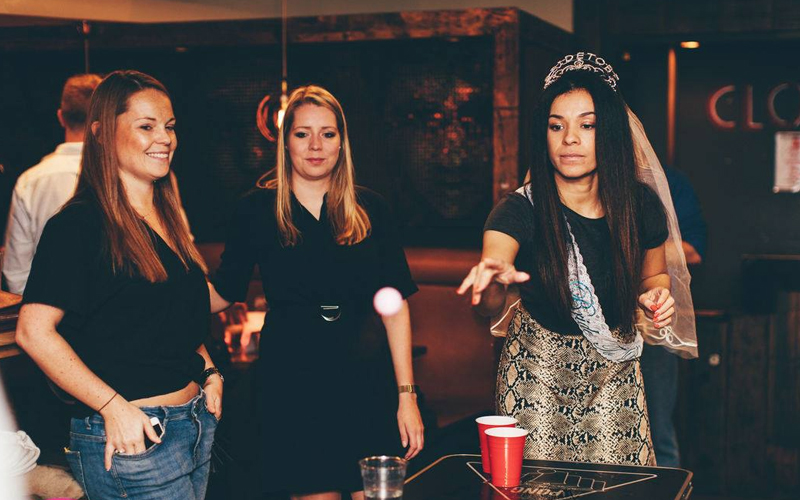 A group of women playing beer pong