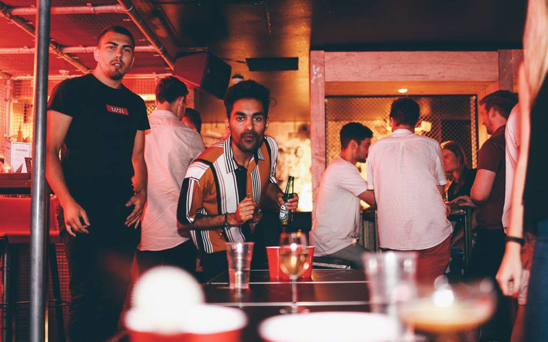 A man playing beer pong as his friend watches
