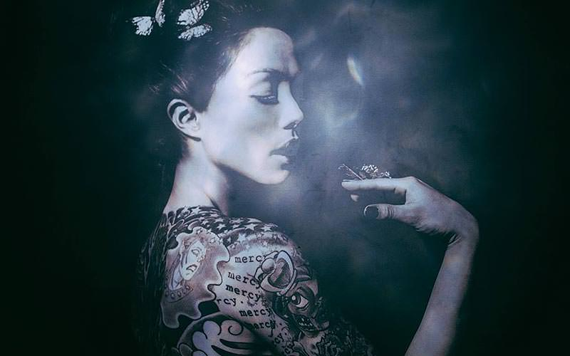 Profile of a woman holding her hand to her face to a smoky backdrop