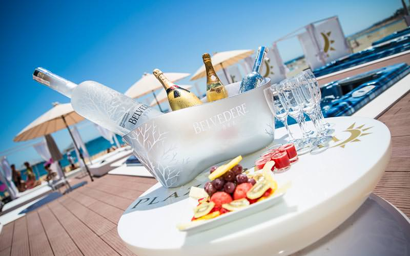 Champagne and vodka in an ice bucket on a table, alongside champagne glasses and a platter of fruit