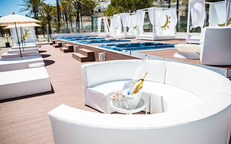 A table topped with champagne and a bottle of vodka in an ice bucket, in a white booth with sun beds in the background