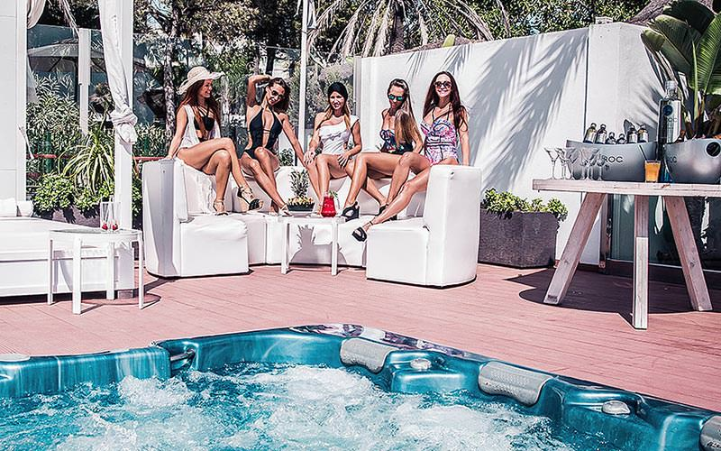 Five women posing on a sunbed with a Jacuzzi in the foreground