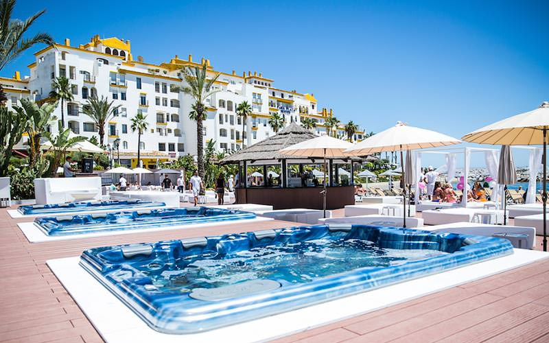 Jacuzzis in the floor surrounded by white sunbeds under canopies