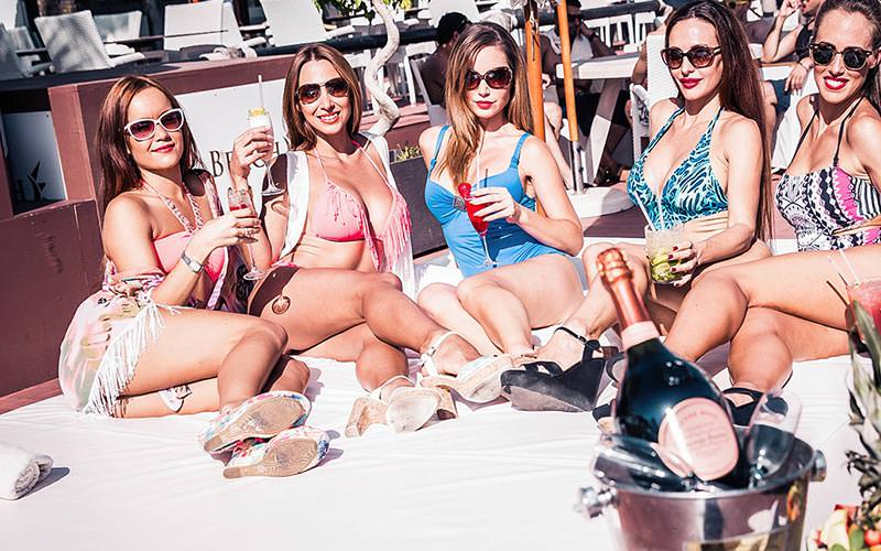 Five women posing with champagne whilst sat on a sunbed