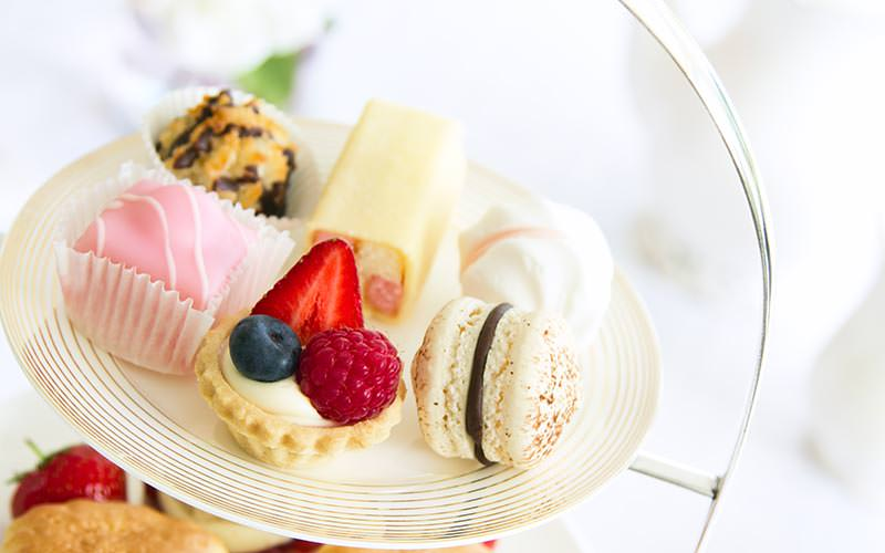 An areal shot of some delicate treats on a high tea plate