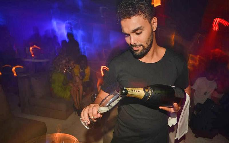 A barman pouring a bottle of Moet into a champagne flute
