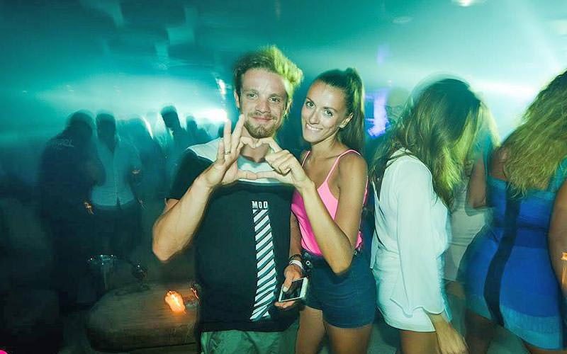 A girl and a boy in a club making their fingers into a heart shape