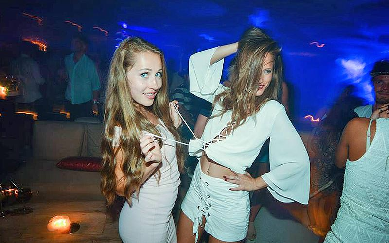 A girl pulling another girl's top, in a nightclub