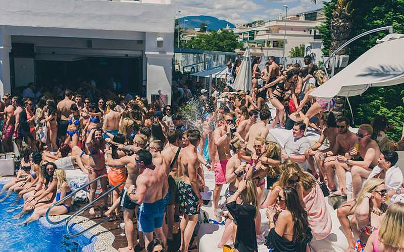 People dancing and stood around the pool at Sisu